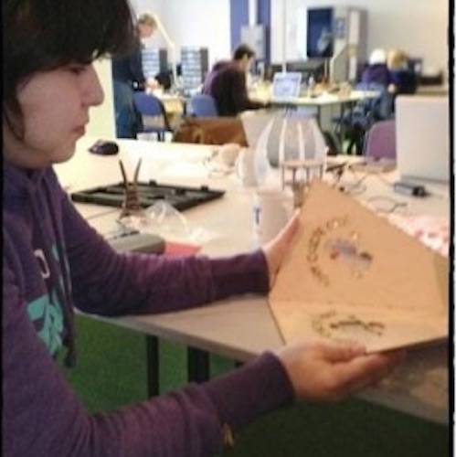 image of a participant holding plywood with the fca logo laser cut