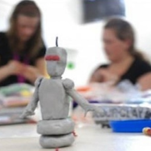 image of a plasticine robot in the foreground and two participants in the background