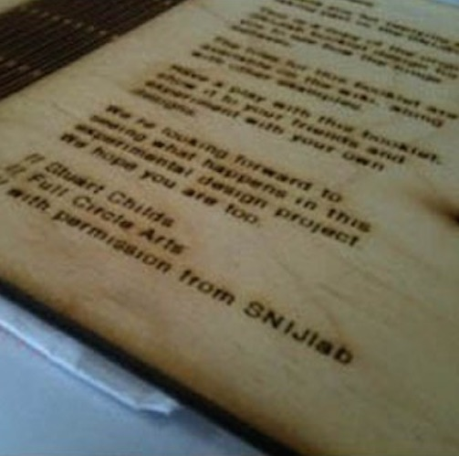 image of a plywood note book laser printed with details about the project