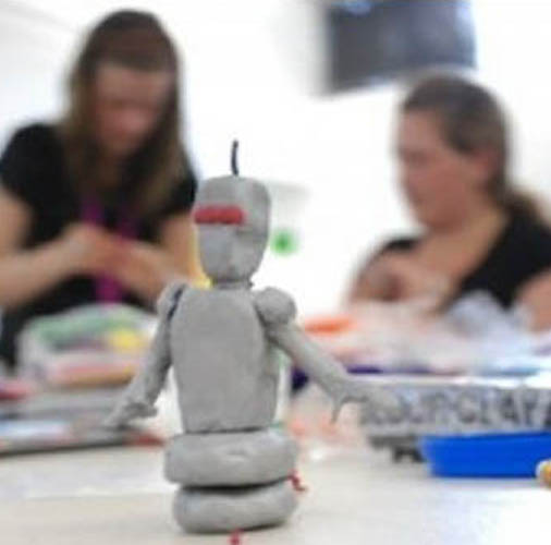 image of a plastic robot in the fore ground and two people in the background working