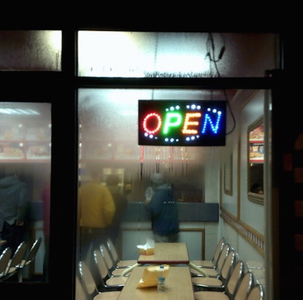 images looking through a cafe window at night. the open sign is lit up in neon colours