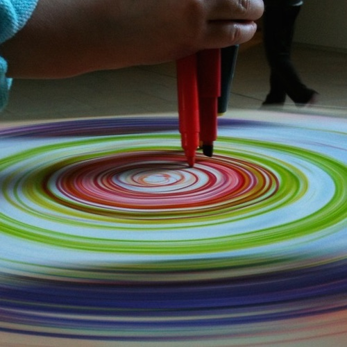 image of pens being held down while a wheel spins paper and circular marks are made on the paper