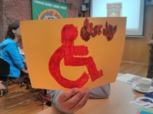 a photo of someone holding up the accessible wheelchair sign to the camera