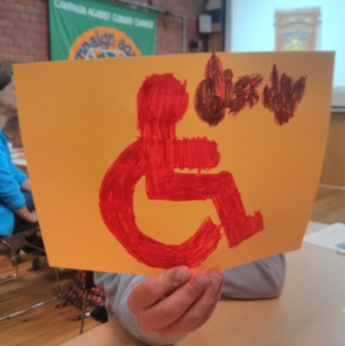 participant to the protest banner workshop holding up to the camera his banner idea of the wheelchair accessible sign