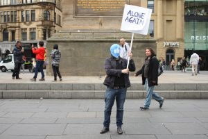 image of a man holding a sign saying 'alone again. he's wearing a mask with the facebook like symbol on