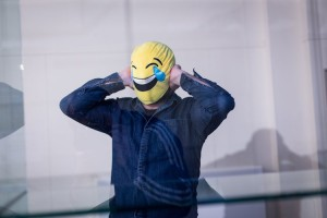 a man with a laughing emoticon mask over his head