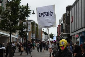 man holding up a sign saying 'empathy'. he has a mask on with the smiley face Emoticon on it