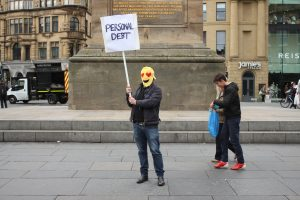 a man wearing a mask with a sign saying 'personal debt'. his mask is love heart Emoticon