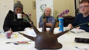 a photo of three people sat around a table. In the centre of the table is a hat with spikes on it, each spike holds a flower