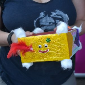 A person holding a box decorated in gold and glitter. it has a smiley face on it