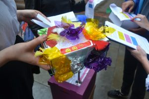 a decorated box covered in tin foil, coloured paper and smiley faces