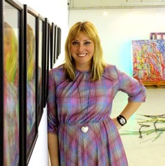 photo of jenny drinkwater leaning against her art in frames on the wall to the left of her