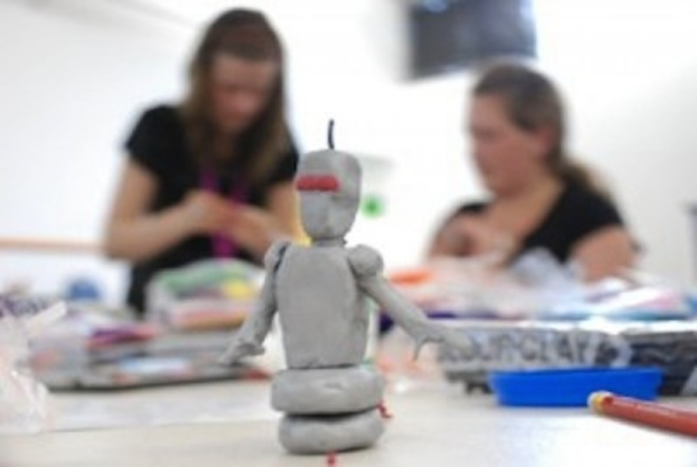 Photo of two young people in the background and a plasticine model of a robot in the foreground